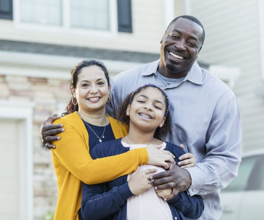 An 11 year old mixed race Hispanic and African-American girl standing with her parents outside their home. Mom is a mature Hispanic woman and dad is a mature African-American man. They are both in their 40s, happy and proud of their daughter.  All are smiling at the camera.